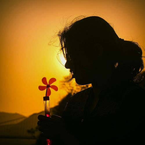 Close-Up Of Silhouette Woman Holding Pinwheel Toy Against Clear Orange Sky