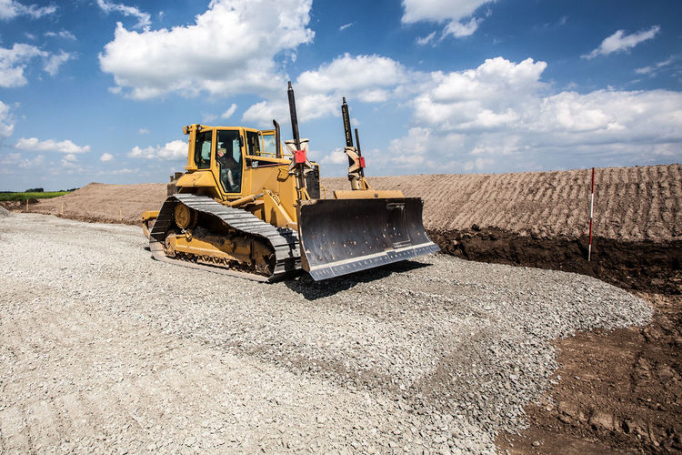Man Driving Bulldozer At Construction Site Against Sky