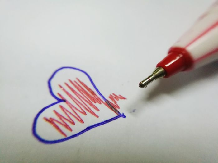 Cropped Image Of Pen By Heart Shape With Pattern On Paper