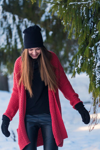 Young beautiful woman wearing warm clothing on snowy field