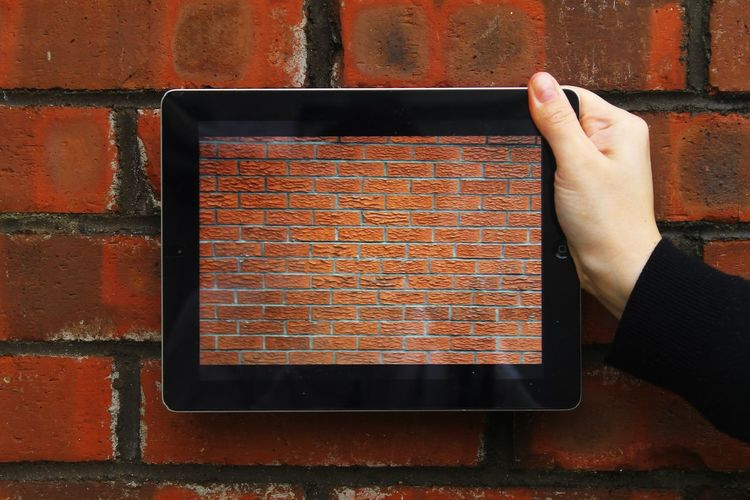 Cropped Image Of Hand Holding Digital Tablet With Brick Wall Picture