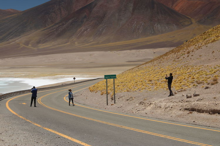People walking on road against mountain