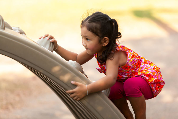 Girl playing on play equipment at playground