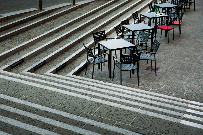 Seat Empty Absence Chair Table No People High Angle View Staircase Day Built Structure In A Row Arrangement Outdoors Pattern Footpath Street Cafe Urban Lines Stairs Public Places Street Cafe Tables Chairs Grey