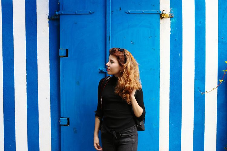 Young woman standing against blue door
