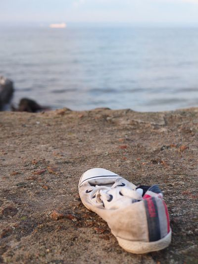 High angle view of shoes on sand at beach against sky