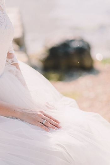 Midsection Of Bride In Wedding Dress