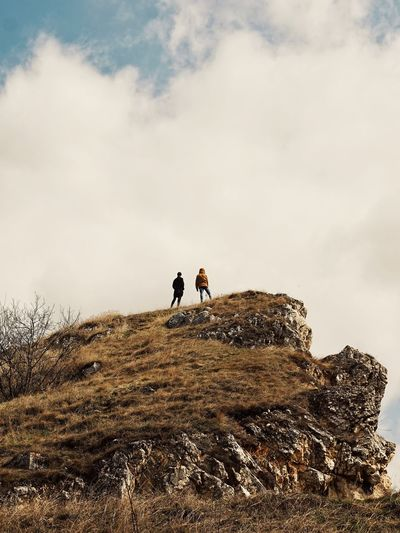 Low angle view of people standing on rock against cloudy sky