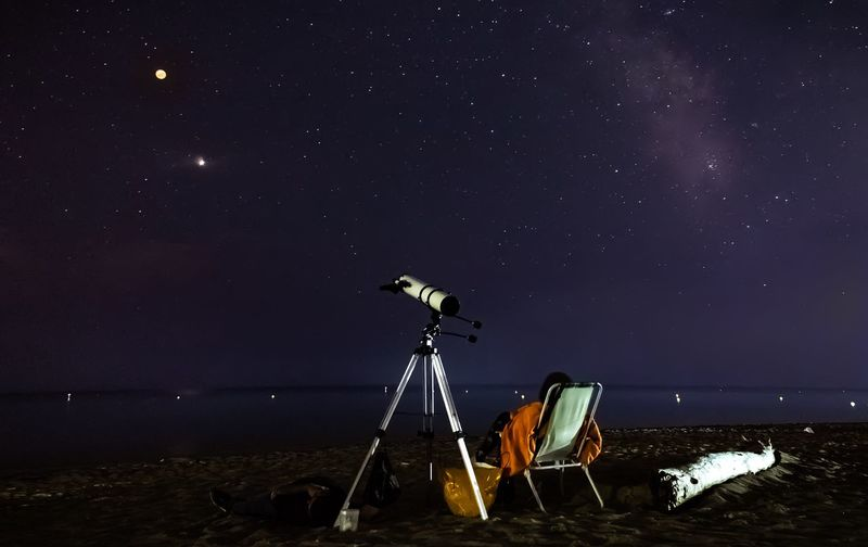 Telescope by deck chair against sky at night