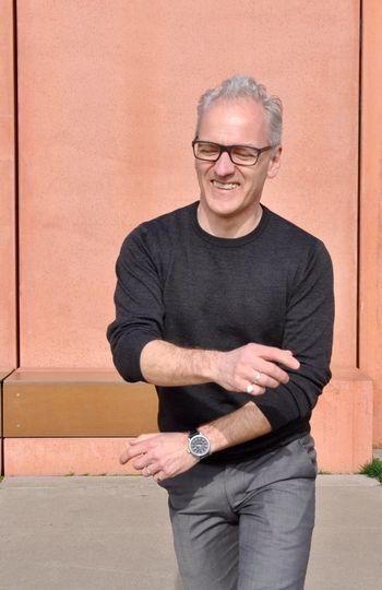 Happy mature man walking against brown wall