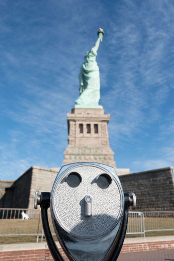 Old tower viewer binoculars in foreground, Statue of Liberty in the background on a sunny day with blue skies on Liberty Island, Manhattan, New York City. Statue of Liberty in profile on her pedestal. Architecture Coin Operated Binoculars Coin Opereted Binoculars Day Ellis Island  Ellis Island / Statue Of Liberty Liberty Island New York New York City New York ❤ New York, New York Outdoors Sky Statue Of Liberty Statue Of Liberty New York Things To Do In New York Tower Viewer Travel Destination Travel Destinations