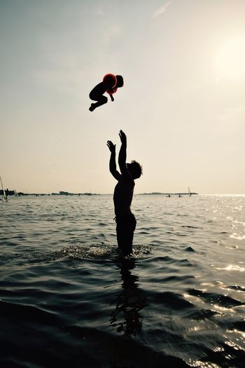 Silhouette Shirtless Father Catching Child While Standing On Sea Against Sky