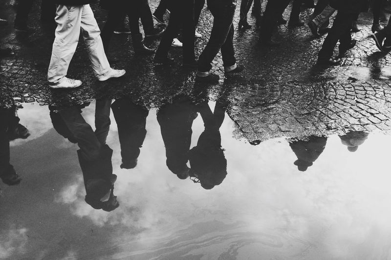 Reflection of people walking on footpath in puddle