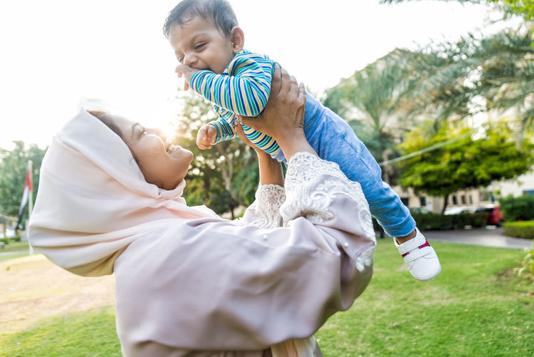Side view of mother holding son mid-air at park