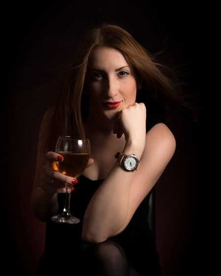 Portrait of young woman holding wineglass while sitting against black background