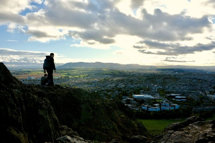 Man standing on rock looking at cityscape against sky