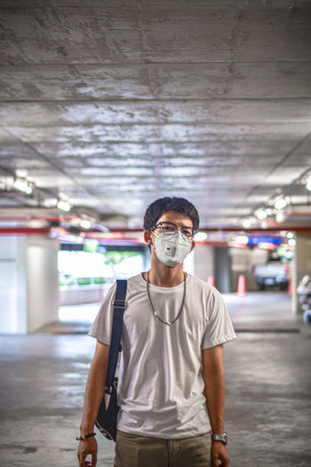 Portrait of young man standing wearing mask standing in parking lot