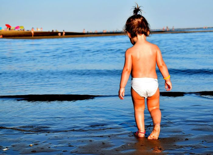Rear View Of Toddler Standing At Beach
