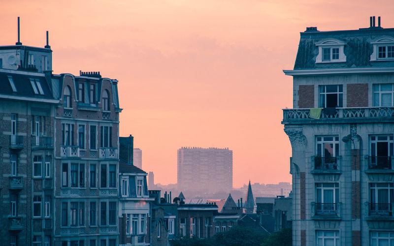 Residential buildings against sky during sunset