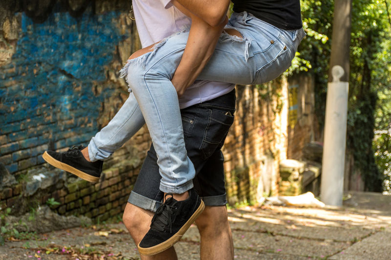 Midsection Of Man Piggybacking Woman While Standing On Road