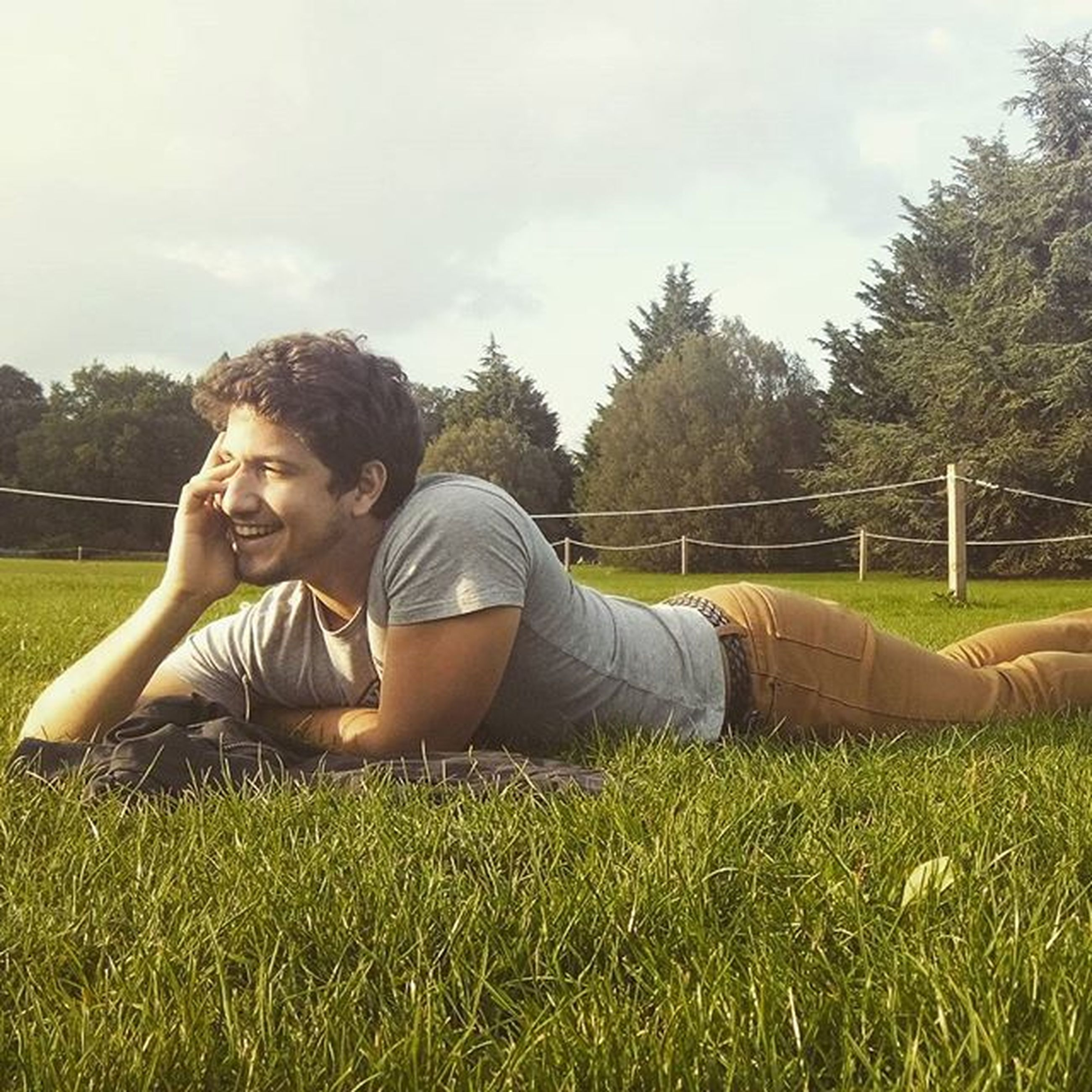 grass, lifestyles, leisure activity, tree, relaxation, person, young adult, casual clothing, sky, sitting, field, grassy, park - man made space, young women, full length, day, green color, lawn