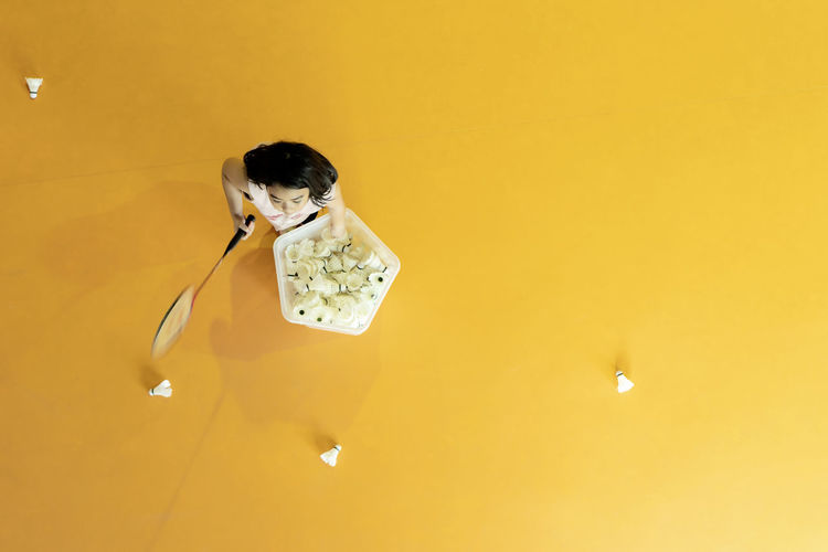 High angle view of girl holding badminton racket an cock against yellow background