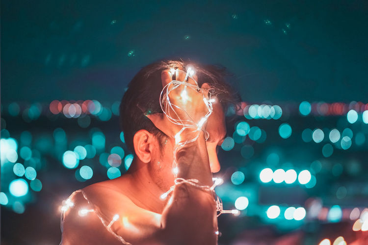 Portrait of shirtless man standing against illuminated light