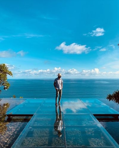 Man standing on glass against sea and sky