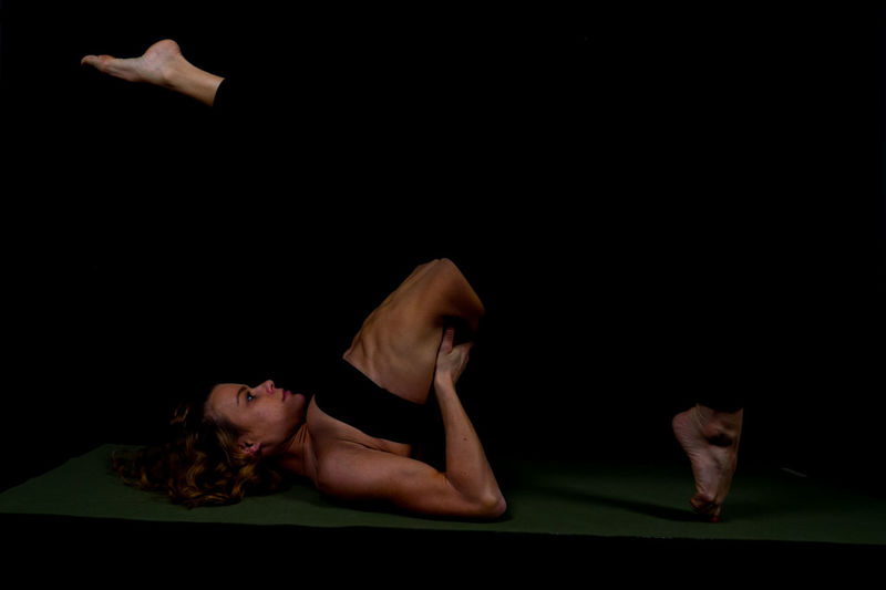 Athlete Exercising On Mat Against Black Background