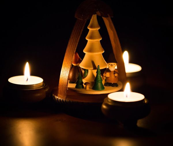 Close-up of christmas decoration with illuminated tea light candles on table