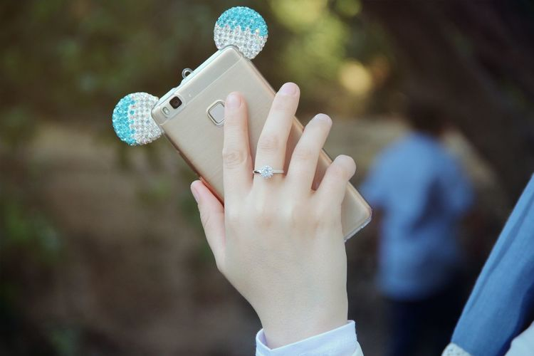Cropped Hand Of Woman Holding Smart Phone