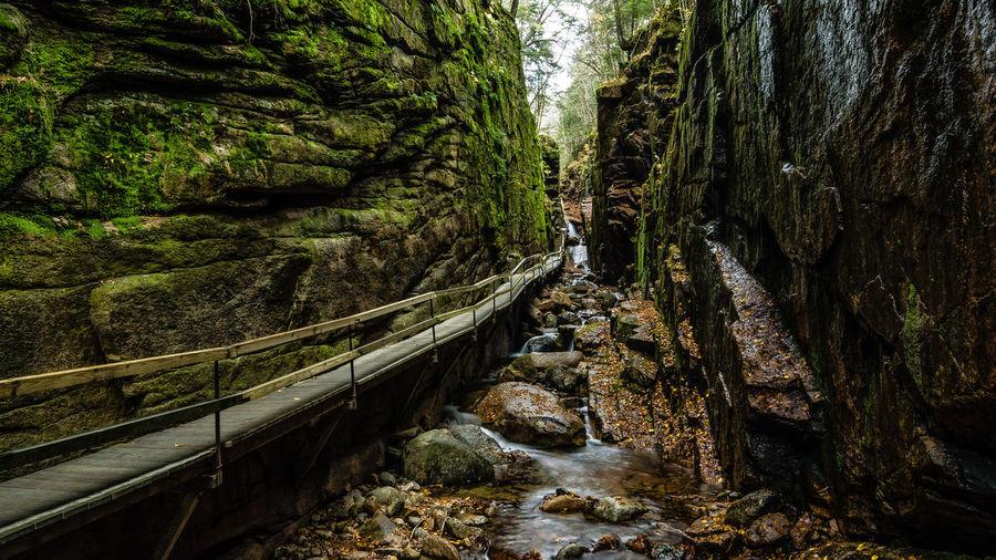Boardwalk By Stream Amidst Rock Formations