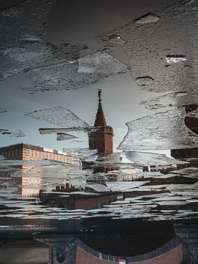 Reflection of building in frozen river