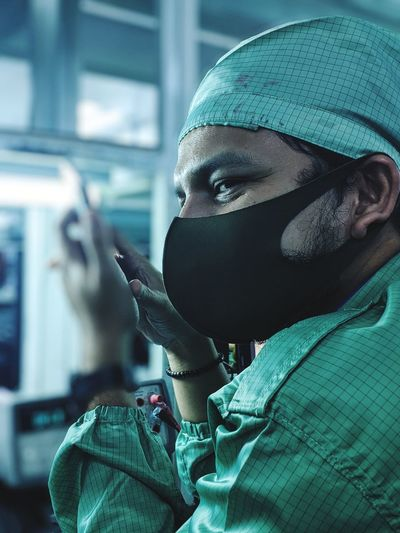 Close-up of doctor wearing protective suit and mask sitting at hospital