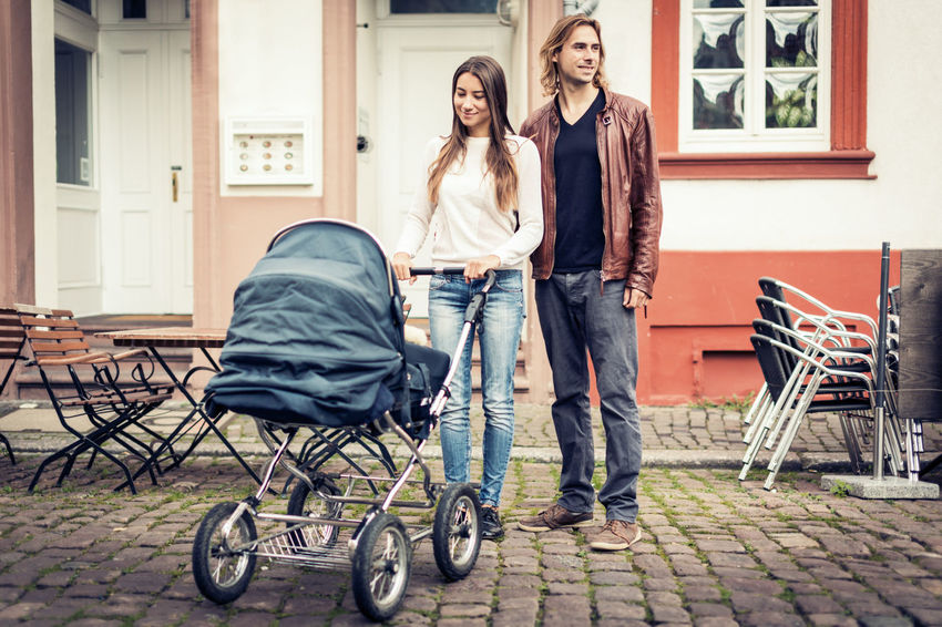 Baby City Life Family Family Of Three Happy Mother Urban Scene Baby Stroller Buildings Father Lifestyles Men Outdoors Parent Parenting Parents People Street Togetherness Two People Women Young Adult Young Family Young Parent