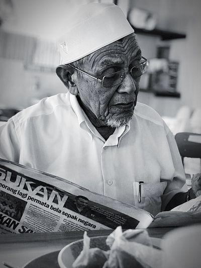 Senior man reading newspaper while sitting at table