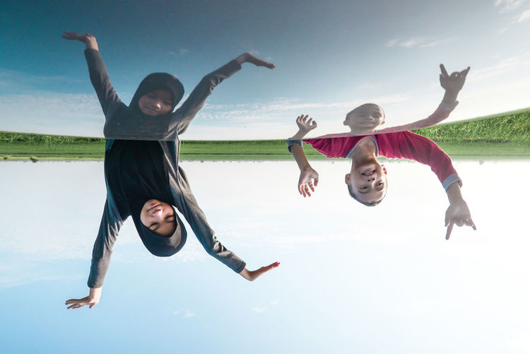 Reflection of siblings with arms raised on car roof against sky