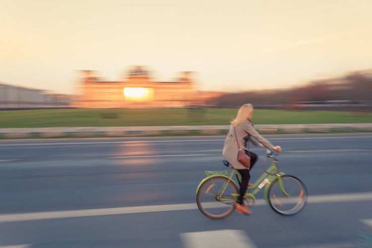 Woman Cycling On Road By Illuminated Reichstag Building