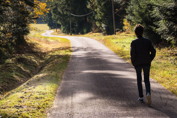 Alone Teenager Boy Leaving Nostalgia Rear View Tree Plant Direction One Person Road Transportation The Way Forward Full Length Nature Sunlight Real People Men Day Shadow Growth Lifestyles Diminishing Perspective Solitude Outdoors Countryside vanishing point Green Grassland Greenery