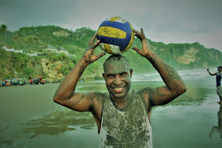 Portrait of messy man holding volleyball while standing on land against mountains and sky