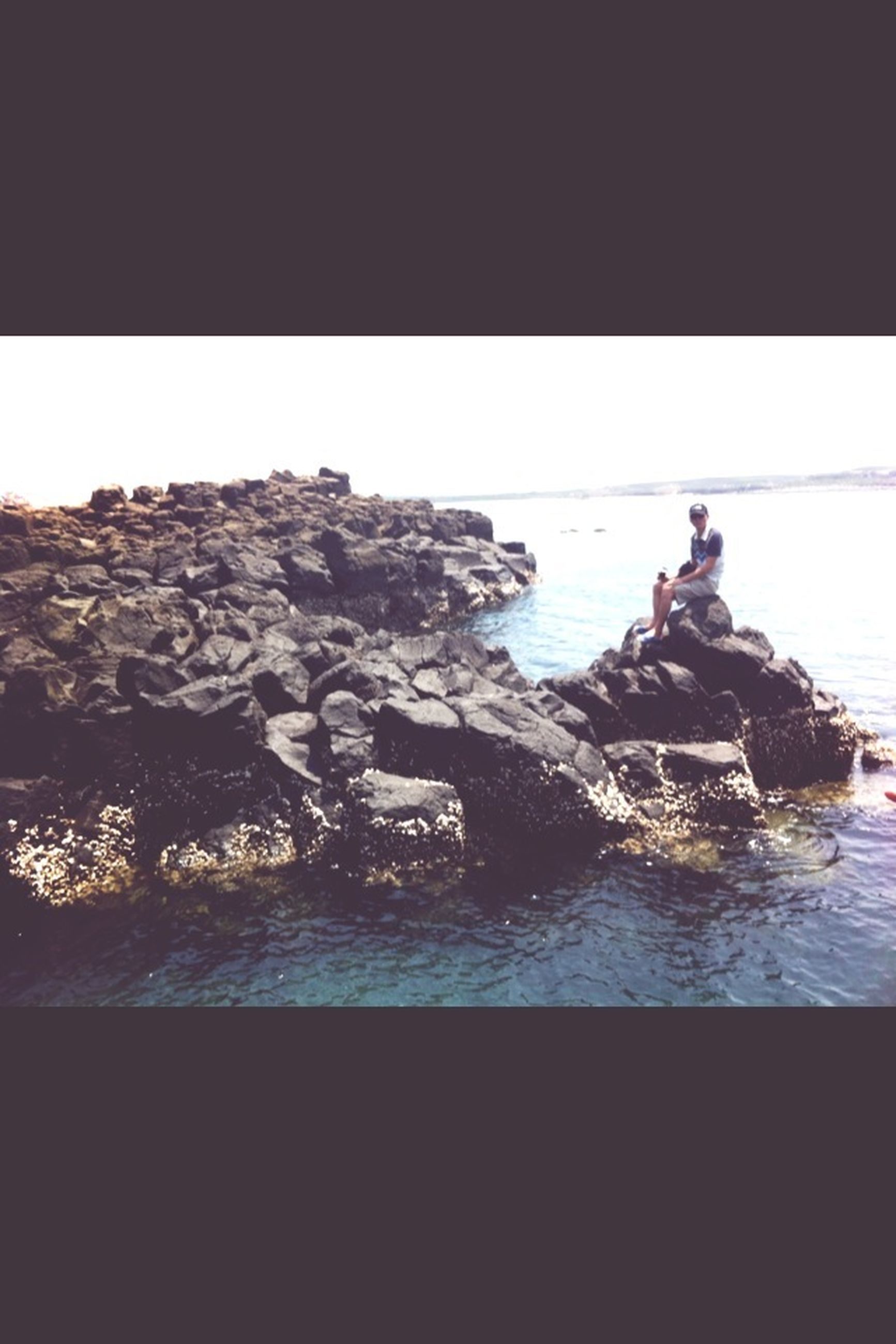 water, sea, rock - object, clear sky, beauty in nature, nature, horizon over water, tranquility, copy space, transfer print, scenics, tranquil scene, rock formation, auto post production filter, waterfront, men, lifestyles, leisure activity, rock