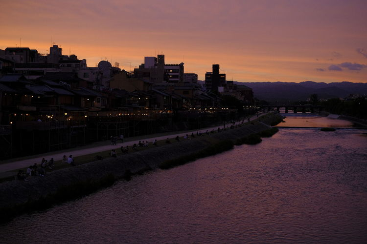 River amidst buildings against sky at sunset