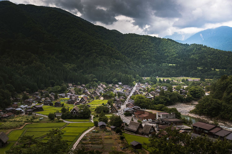 High angle view of townscape by mountain against sky