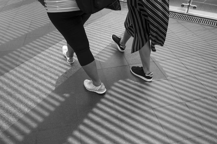 Low Section Human Leg Real People Human Body Part Women Body Part High Angle View Pattern Lifestyles Adult Walking Shadow People Shoe Two People Indoors  Day Sunlight Togetherness Casual Clothing Flooring Human Foot
