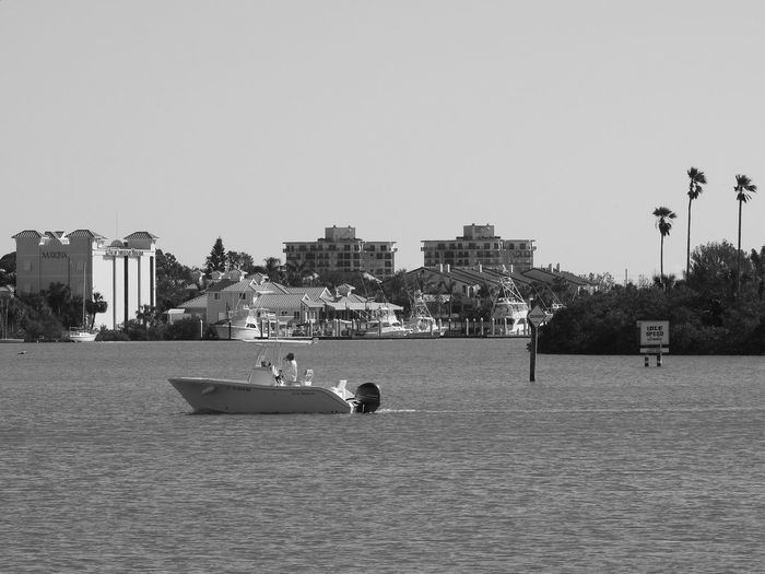 One Person Nautical Vessel Boat Boating Leisure Activity Water Atlantic Ocean Inlet Sign Trees Palm Tree Silhouettes Architecture Hotels Homes From The Pier Oceanside Monochrome Black And White Photography