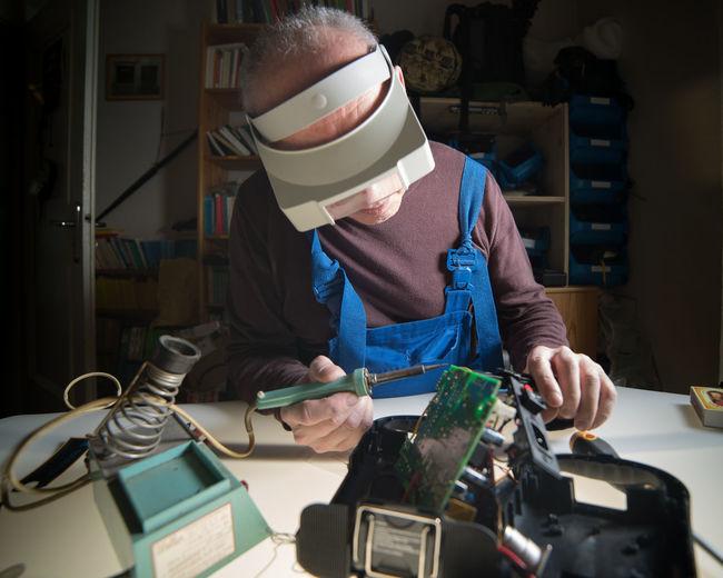 Man repairing circuit board at table