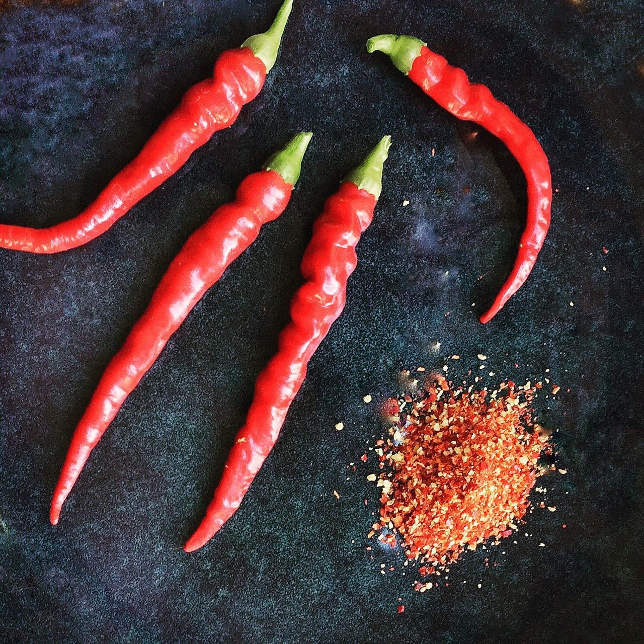 High Angle View Of Red Chili Peppers And Paprika On Table