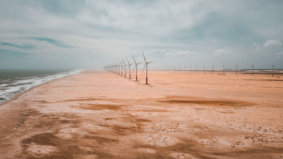 Windmills at beach against cloudy sky