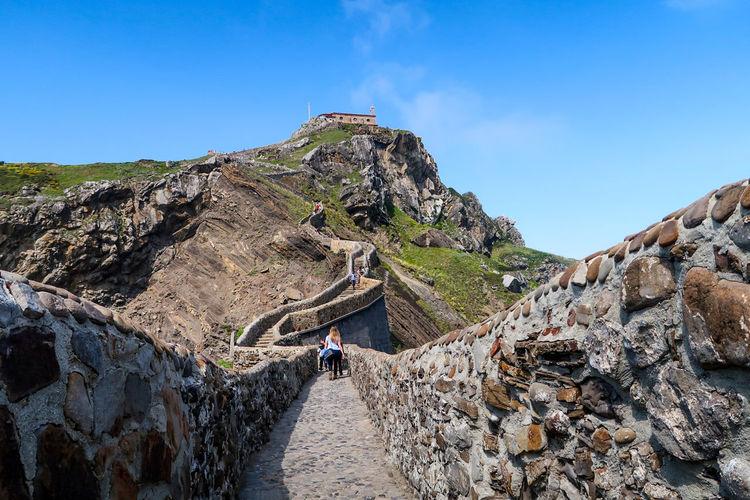 Rear view of people walking on fortified wall