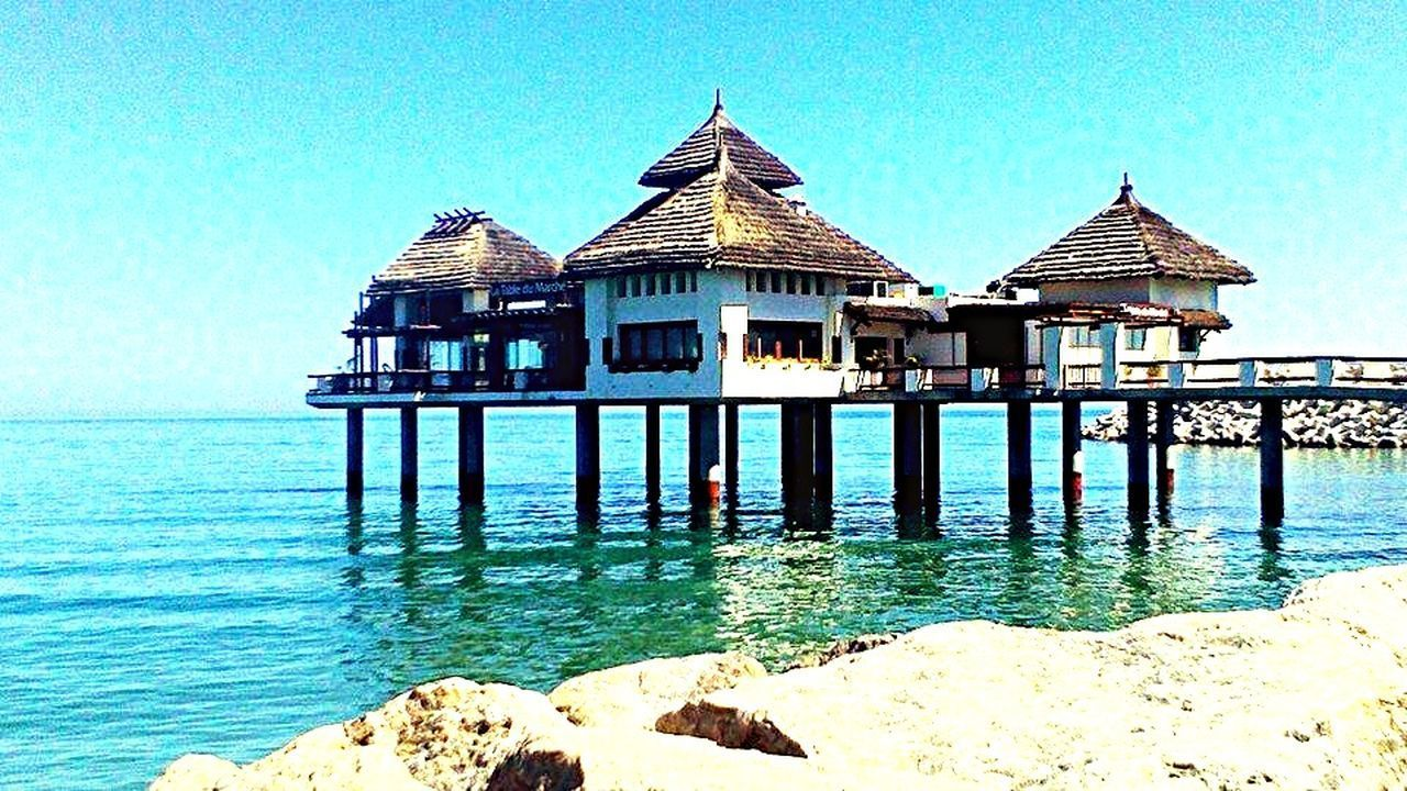 water, built structure, architecture, clear sky, sea, blue, pier, building exterior, wood - material, tranquility, tranquil scene, gazebo, nature, sunlight, scenics, day, outdoors, wooden post, sky, beach